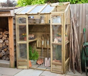 Forest Victorian greenhouse in a garden setting.
